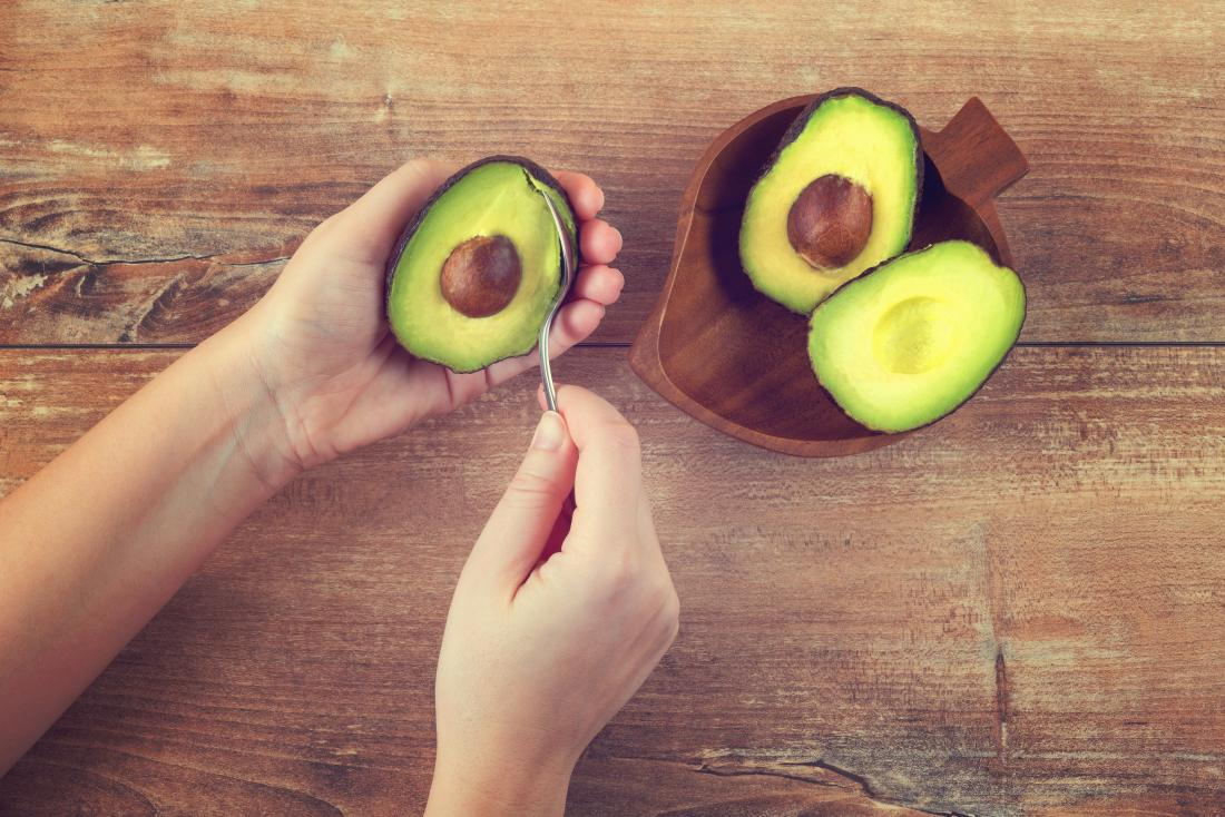 Cut avocados being eaten with a spoon