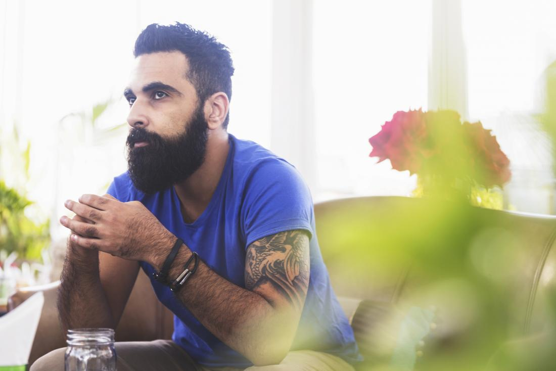 Thoughtful man with tattoos thinking about average penis size