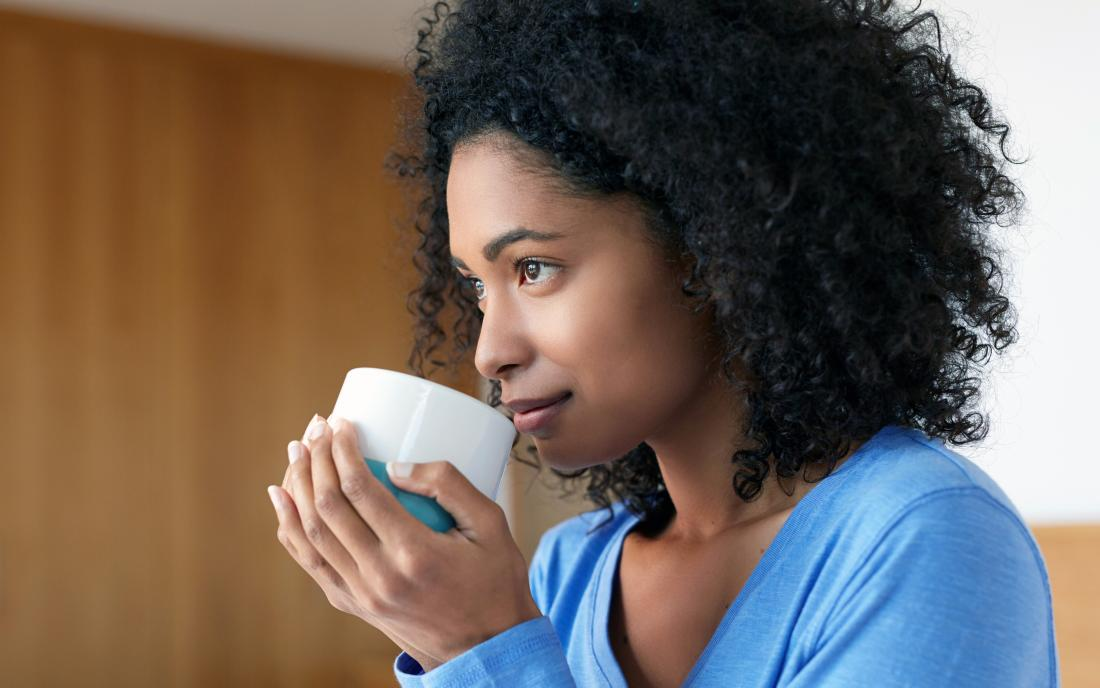 a woman drinking a drink with caffeine out of a mug.