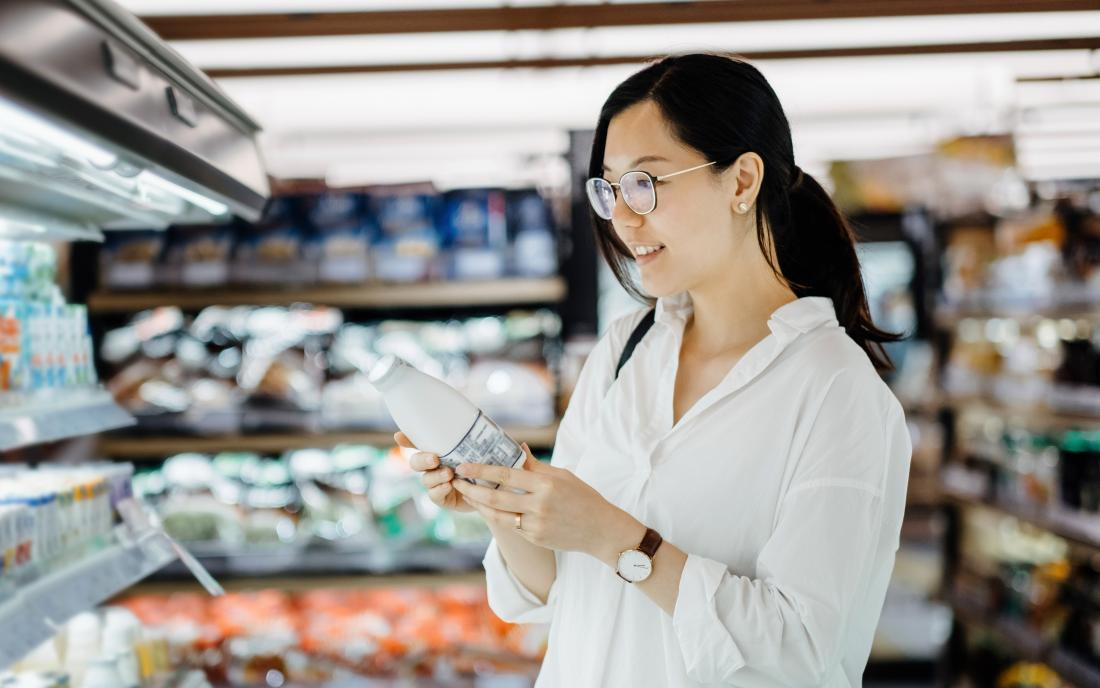 a woman in a supermarket wondering which of the milk substitutes to buy