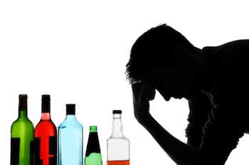 Silhouette of a man holding his head next to a row of empty alcohol bottles