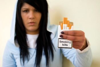 a teenager holding a pack of cigarettes