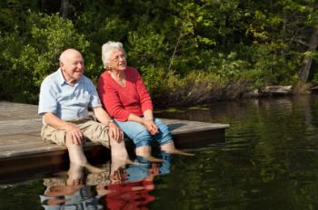 older couple sitting by a lake