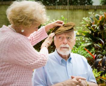 older lady putting a hat on an older man's head