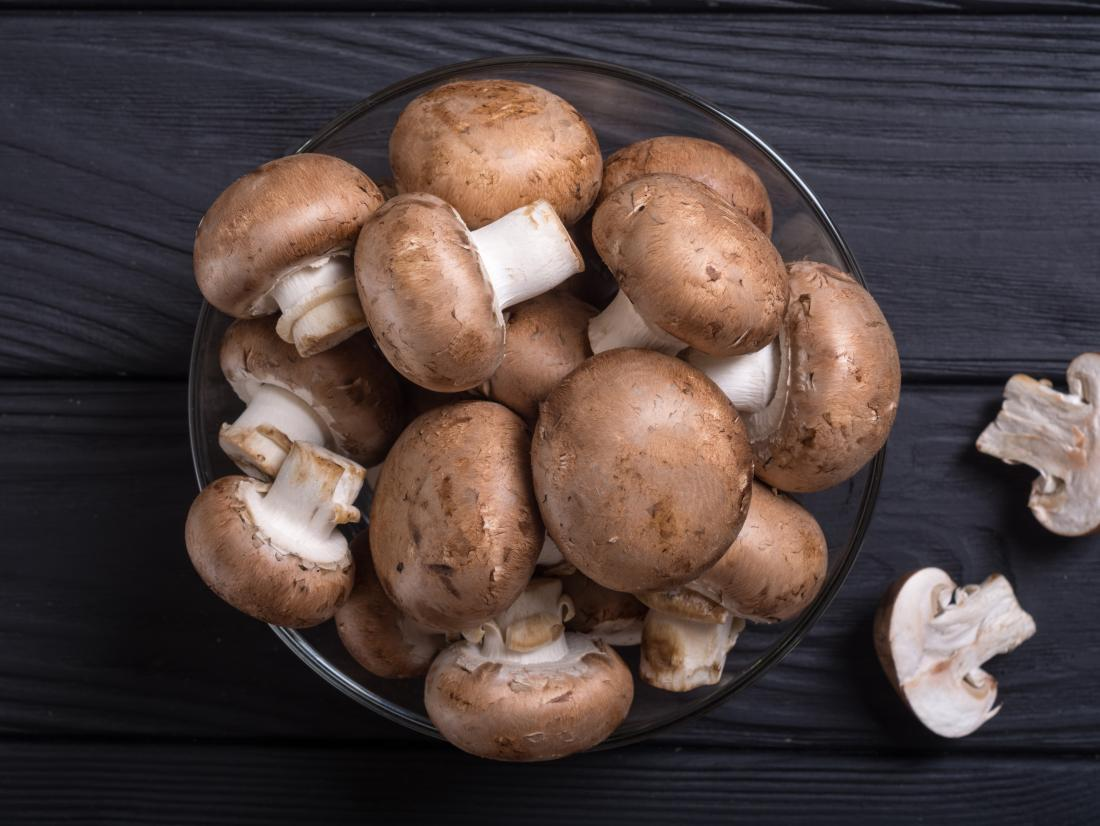 mushrooms in a bowel on a dark table.