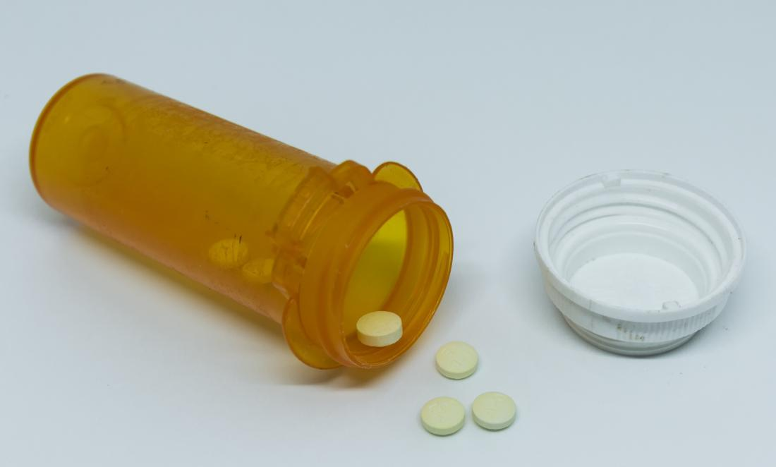 Medication bottle with pill drugs spilling out.