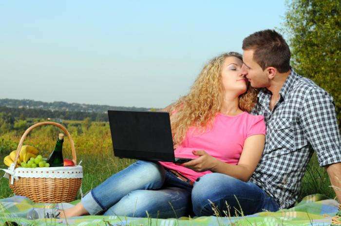 couple kissing while using laptop