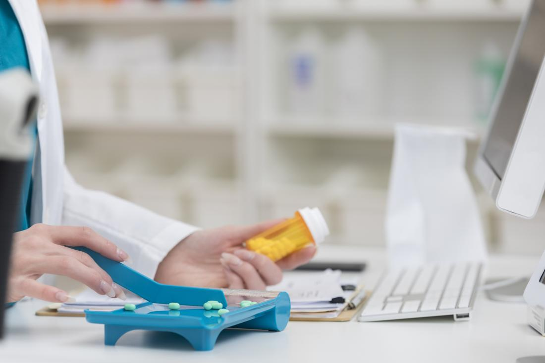 Pharmacist with pills measuring out medication prescription