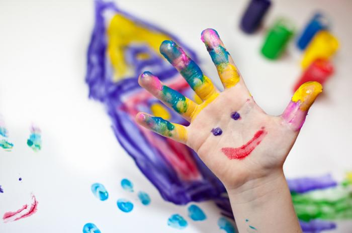 child's hand covered in paint