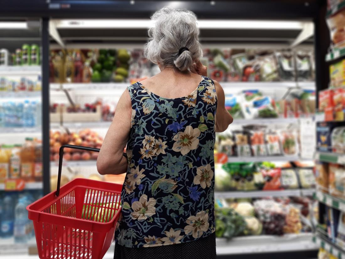 a senior woman in a supermarket looking for products high in iron