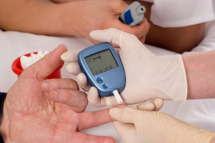 Testing a patient's blood sugar level via finger.