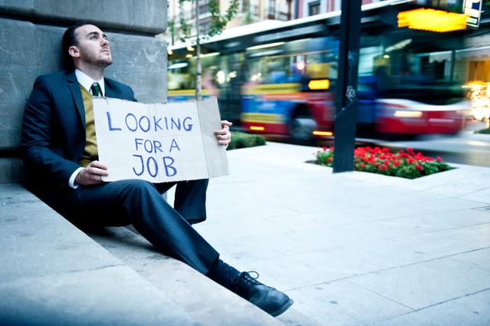 Unemployed man sitting on the street in a suit.