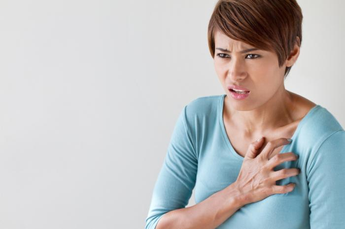 A woman is clutching her chest in discomfort.