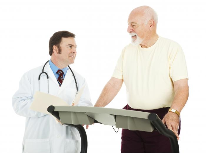 older man on treadmill with doctor assessing