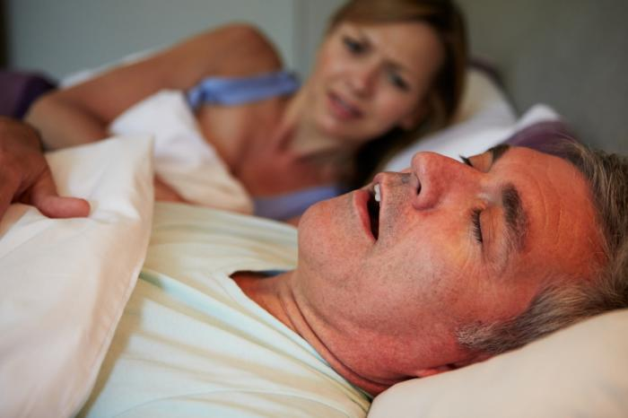A man waking his wife by snoring