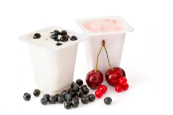Two portions of yogurt with assorted berries.
