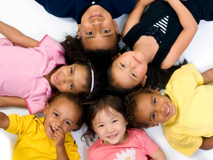 Children lying down in a circle smiling.