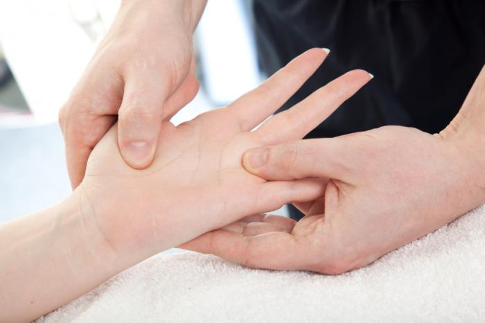 woman receiving physical therapy on hand