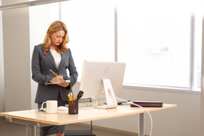 A woman standing at an office desk.