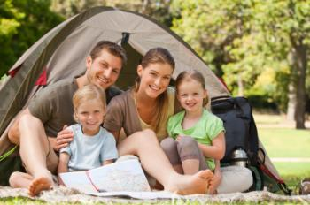 Two parents and two children happy with a tent.