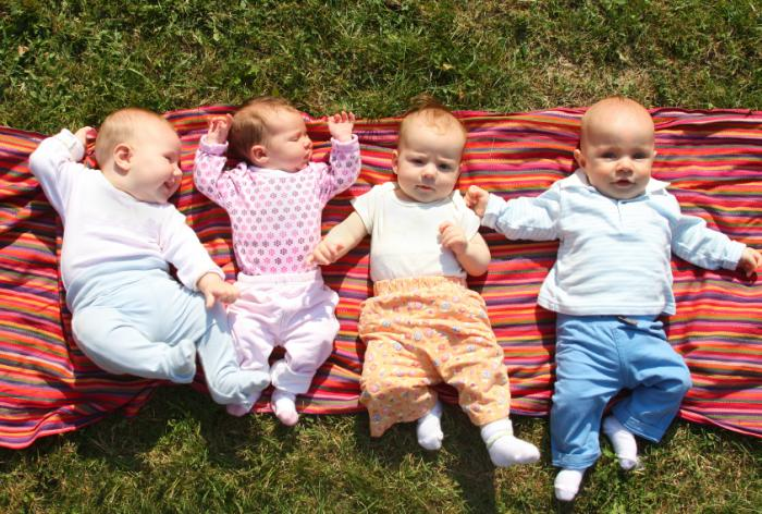 [four babies on a rug outside]