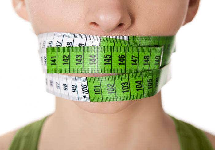A woman with a tape measure around her mouth