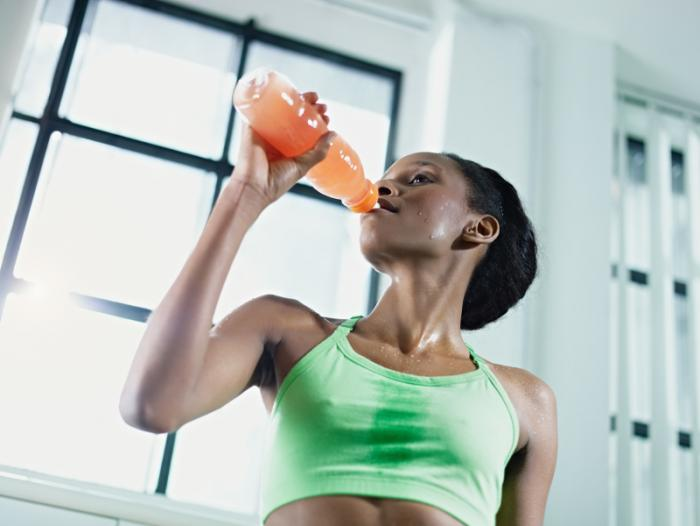 Woman exercising and drinking a sports drink.