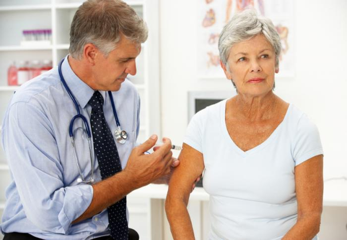 Male physician vaccinating an older lady.
