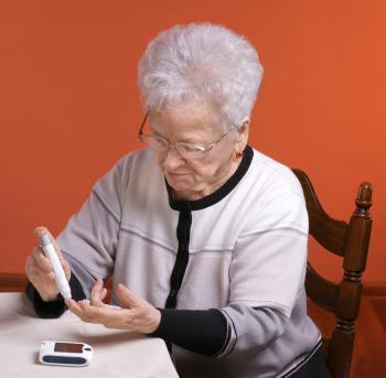 Older lady tests her blood sugar level with a pen device.