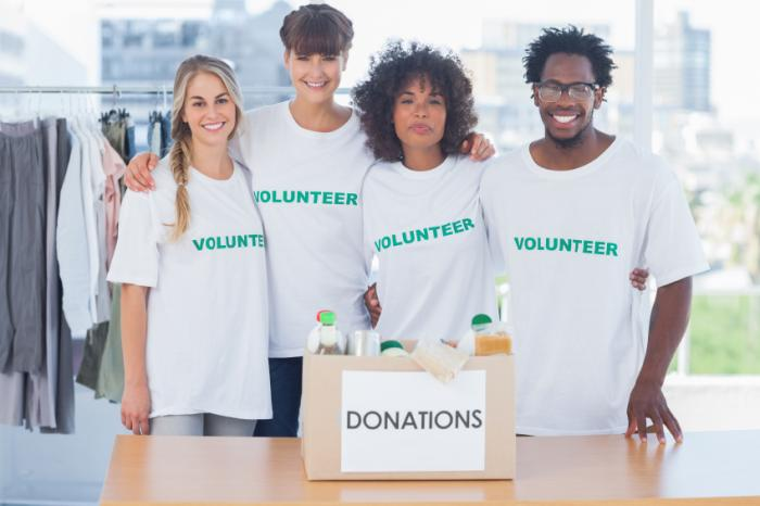 A group of volunteers with a box of donations.