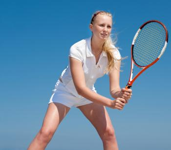A young girl is playing tennis.