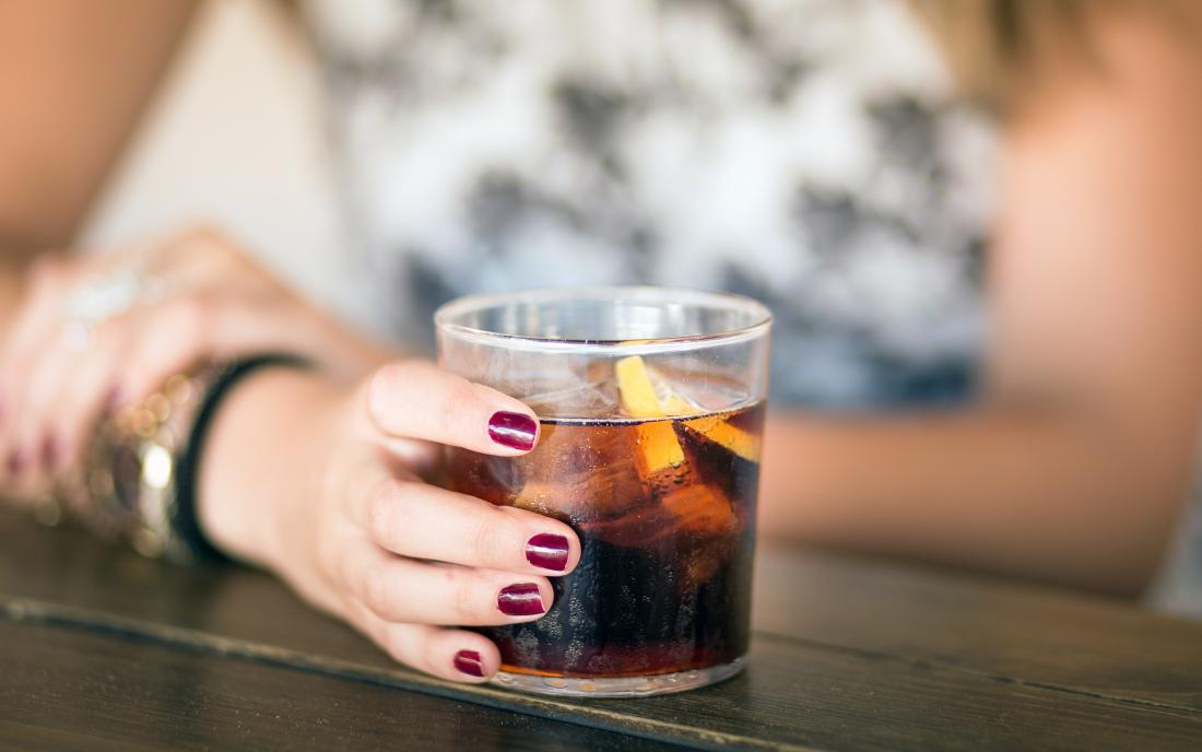 a woman with a glass of coca cola which might be bad for you.