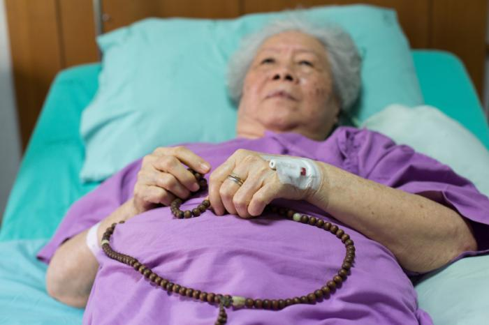 A hospital patient holds onto some prayer beads in bed.