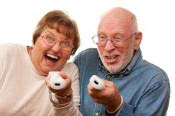 Two older adults holding Wii controllers.