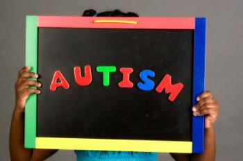 A girl holding an autism sign