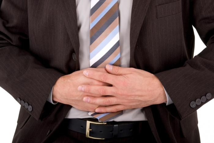 man with nausea holding stomach