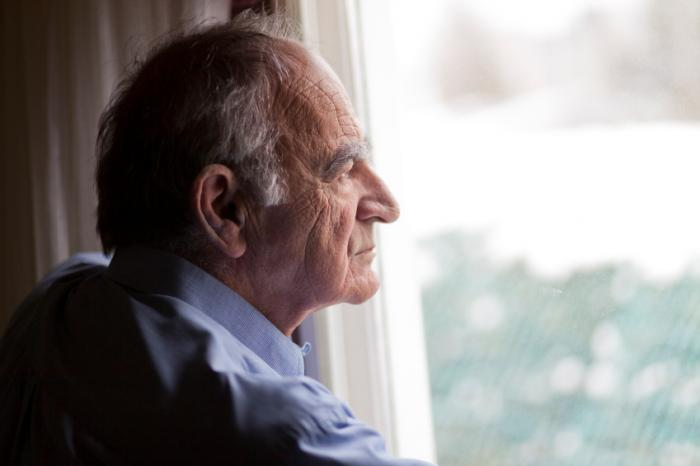 An older man looking out of the window.