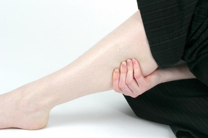 woman clutching painful lower leg