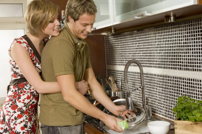 [A woman cuddling partner while he is doing the dishes]