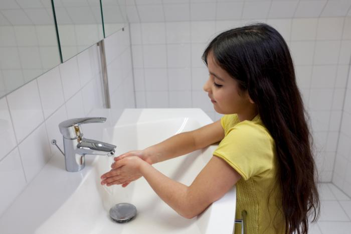 A girl is running her hands under a tap.