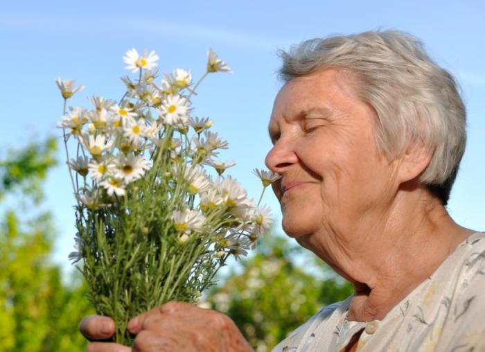 [senior smelling flowers]
