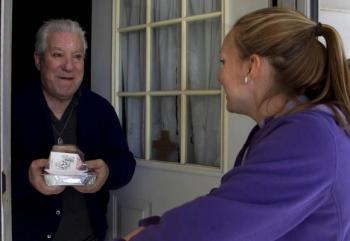 Senior man receives home delivered meal from female visitor