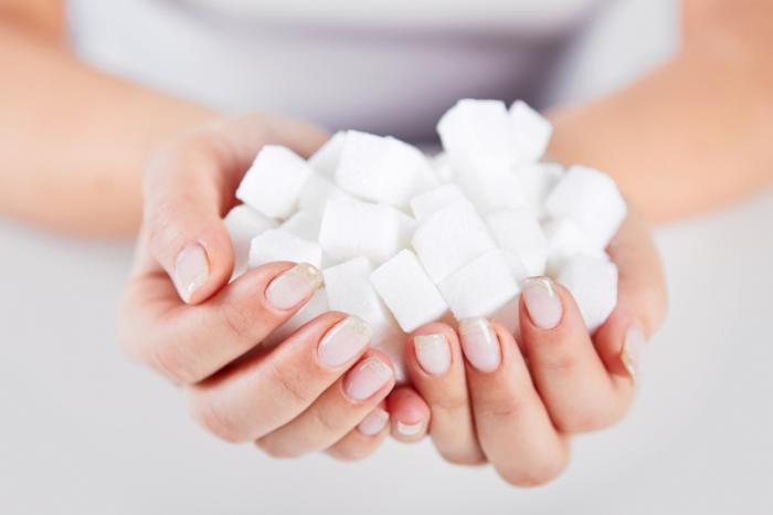 [A woman holding sugar cubes]