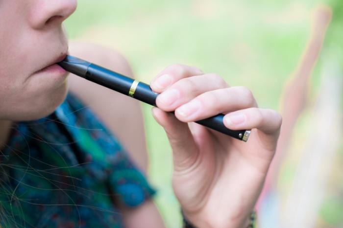 [A teenager using an e-cigarette]