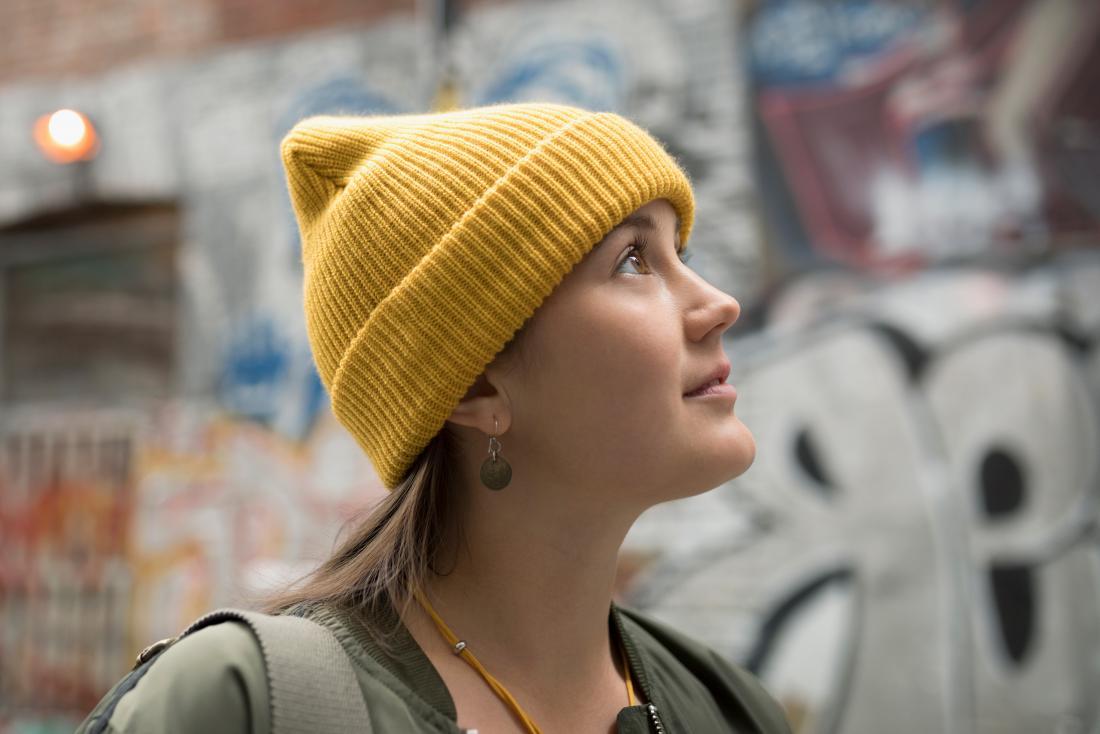노란색 비니를 입은 여자는 낙서로 거리를 걷는 것을 싫어합니다.