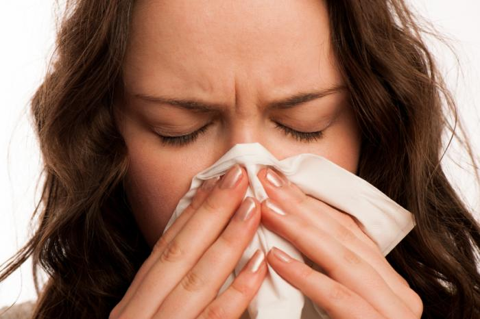 A woman is blowing her nose with a tissue.