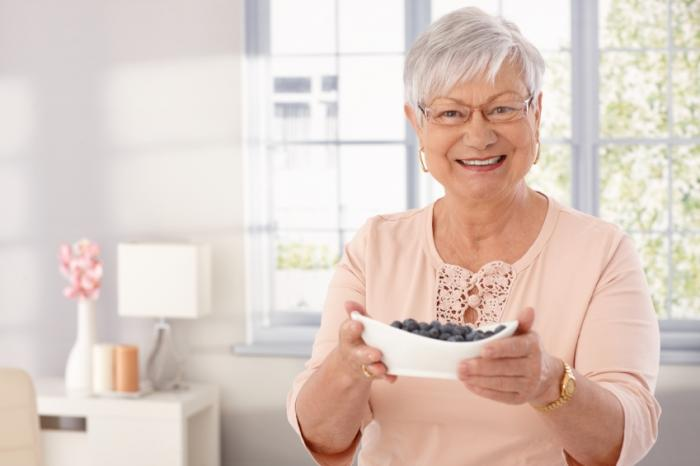 A senior woman is holding a bowl of blueberries.