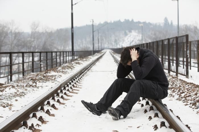 depressed man sitting on train track