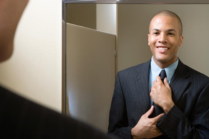 A man adjusting tie smiling in mirror