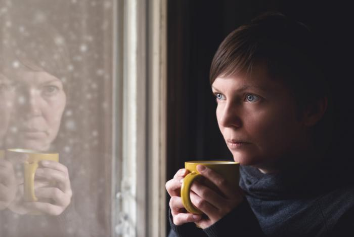 woman staring through window holding cup